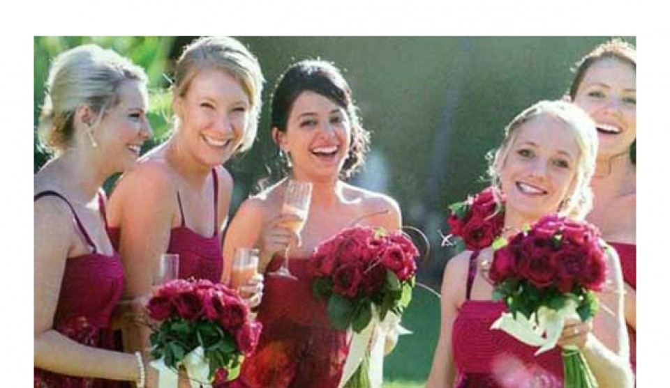 Bridesmaids in burgundy dresses with matching frangipani posies