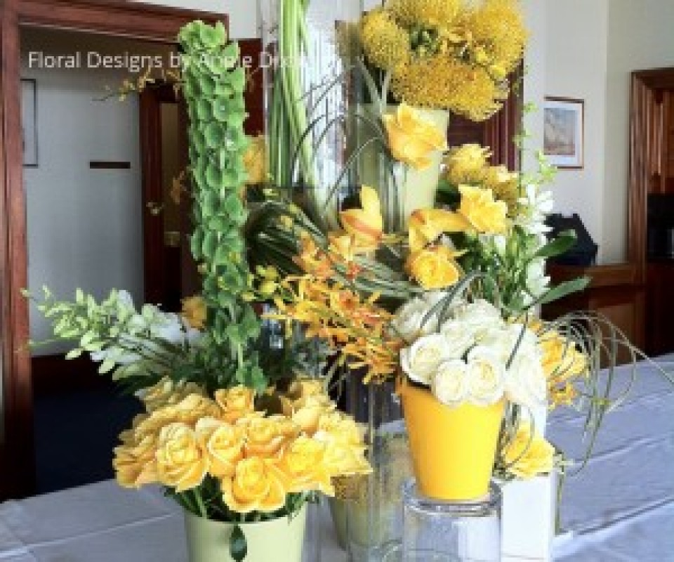 Contemporary buffet table arrangement of yellow and white flowers