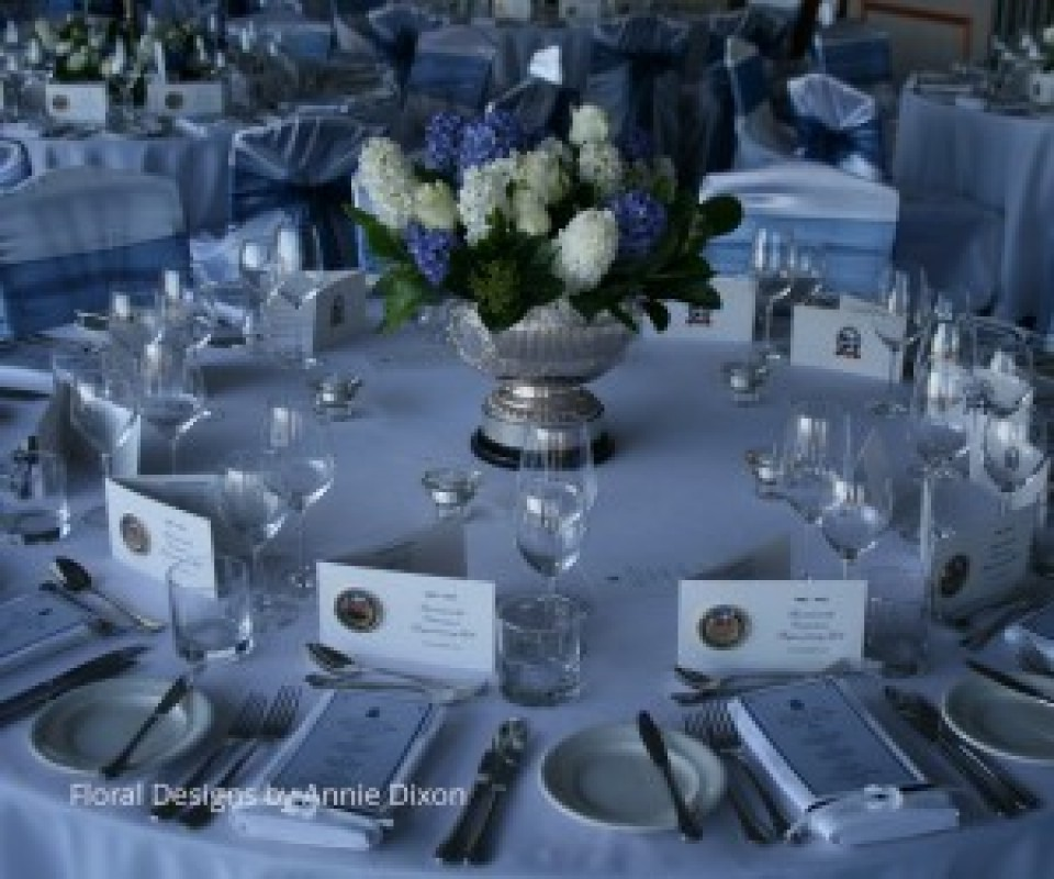 Corporate table arrangement of blue Hyacinths and white Roses in silver trophy