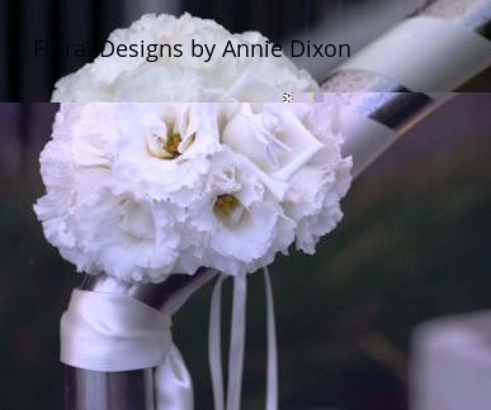 Posy of flowers on railing wrapped in satin ribbon