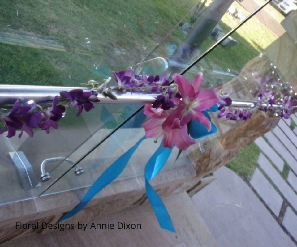 Section of 50m orchid garland entwined around railing