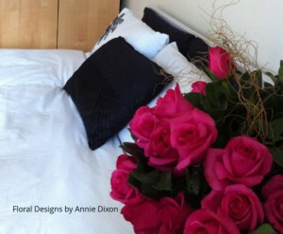 Bedside table arrangement of hot pink roses