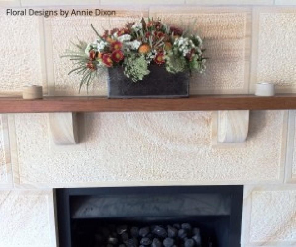 Cottage floral arrangement on wooden mantle over sandstone fireplace