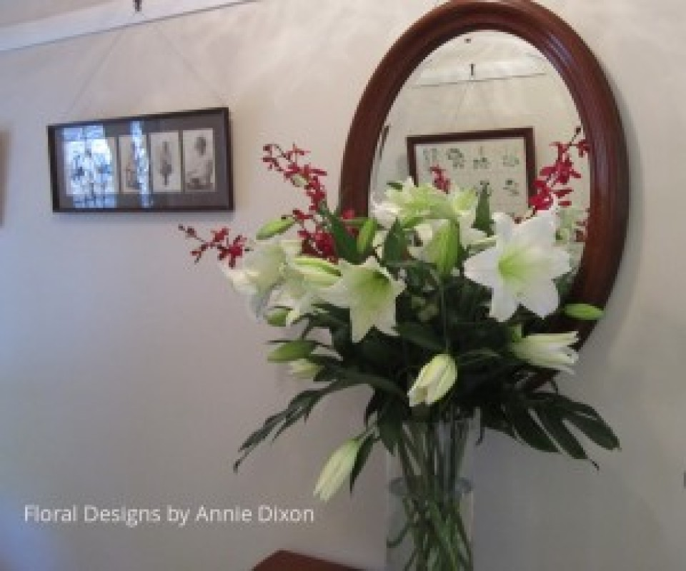 Vase arrangement of November Lilies and Spider Orchids in entrance hall