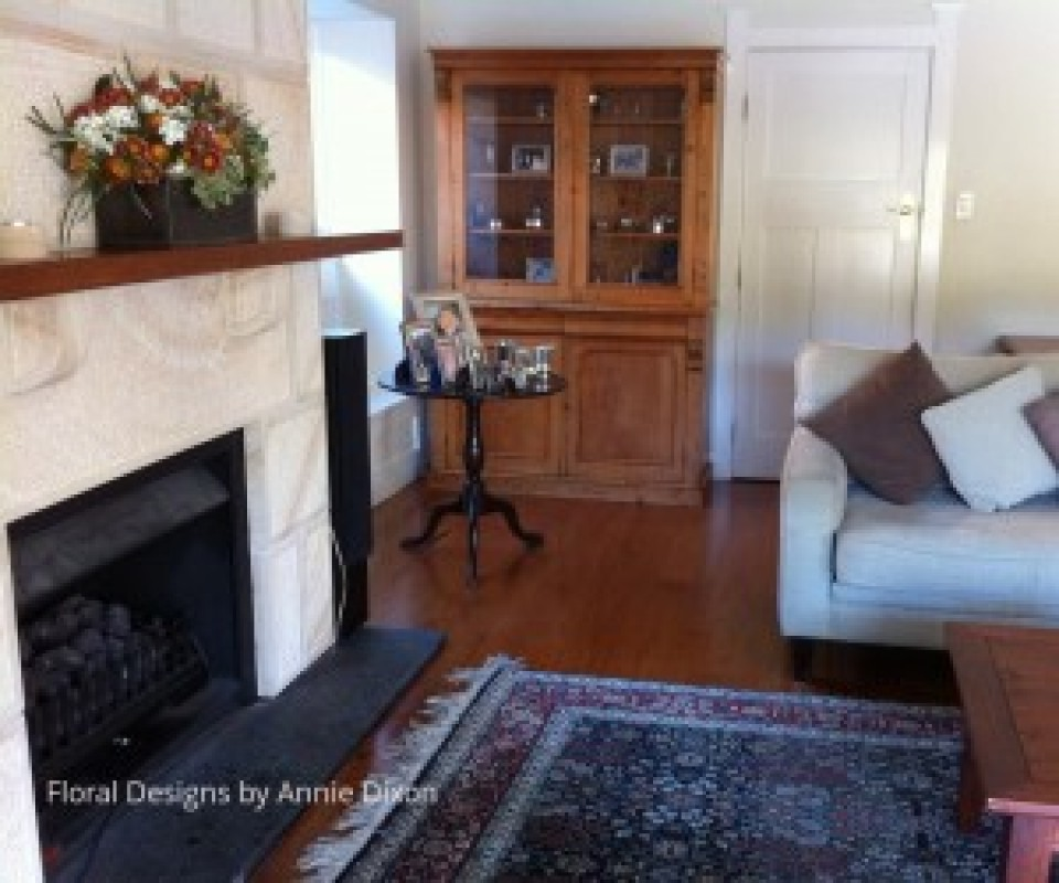 Country style floral arrangement on mantle in lounge room