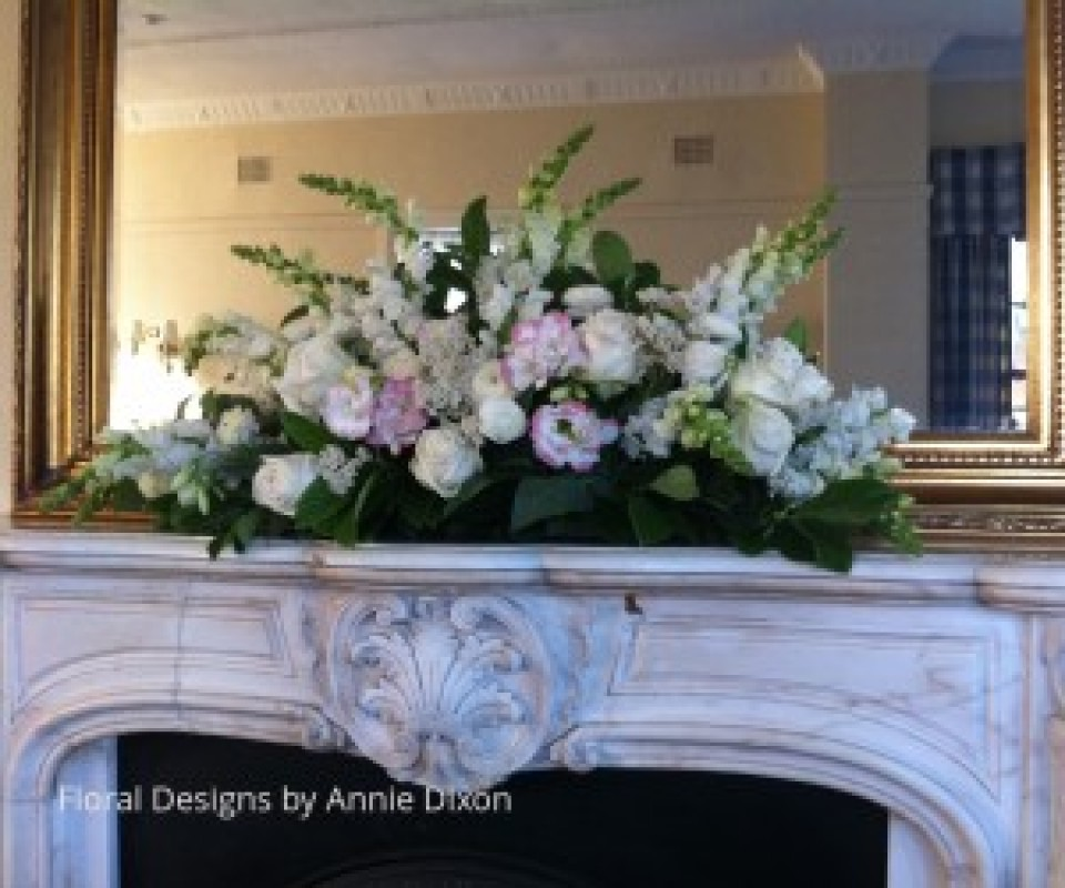 Traditional arrangement of pastal pink flowers on marble mantle