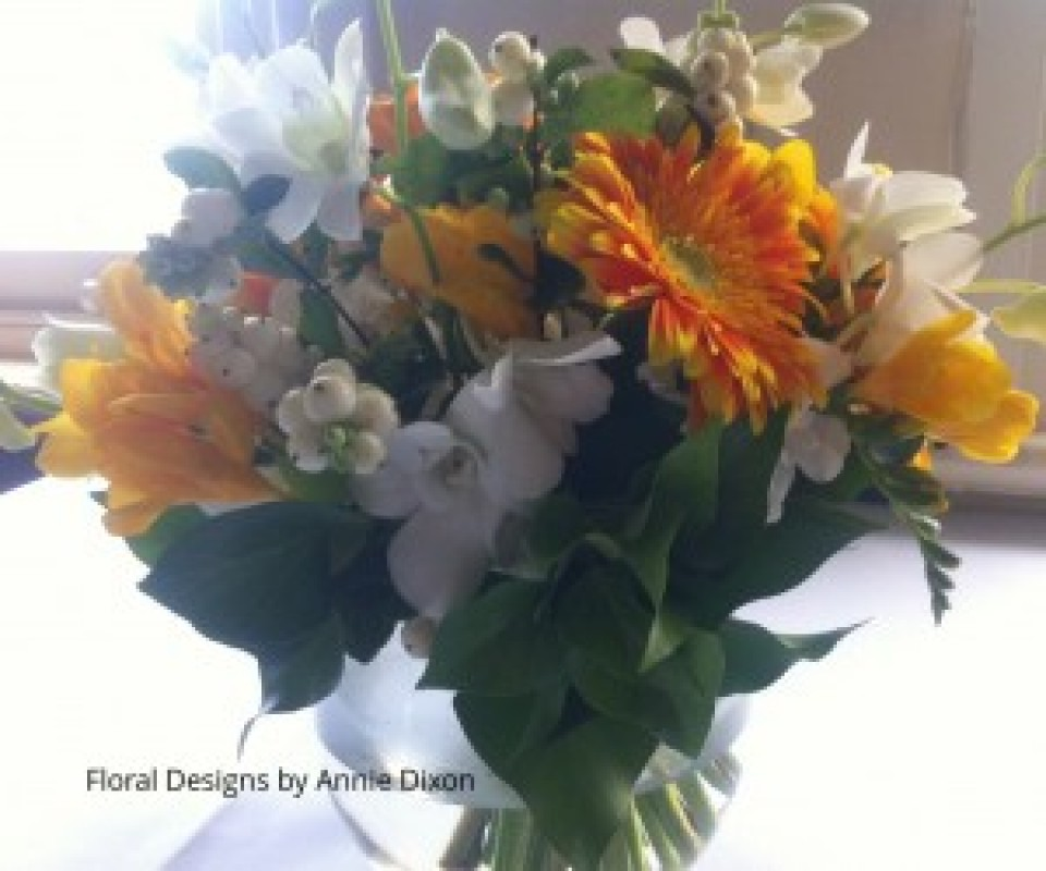 Fishbowl arrangement of yellow Gerberas, Snowberry and Singapore orchids in sunroom