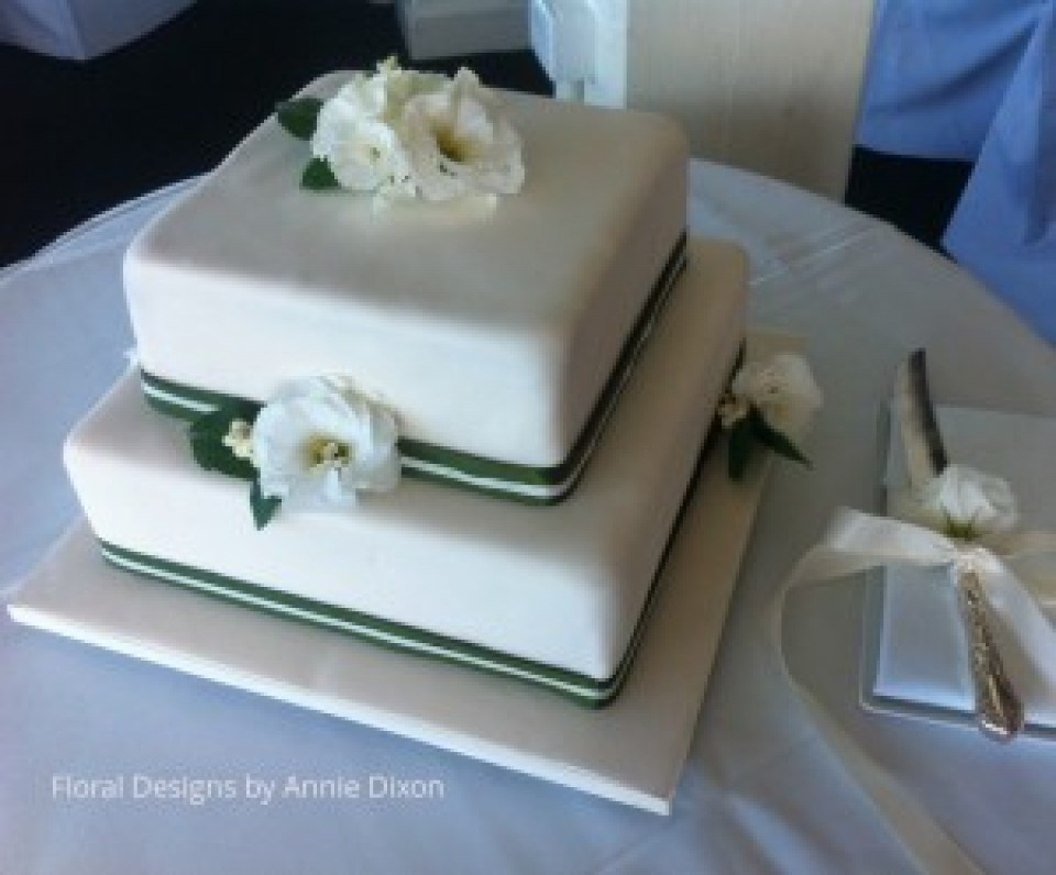 2 tier square wedding cakedecorated with white Lisianthus and green and white ribbon
