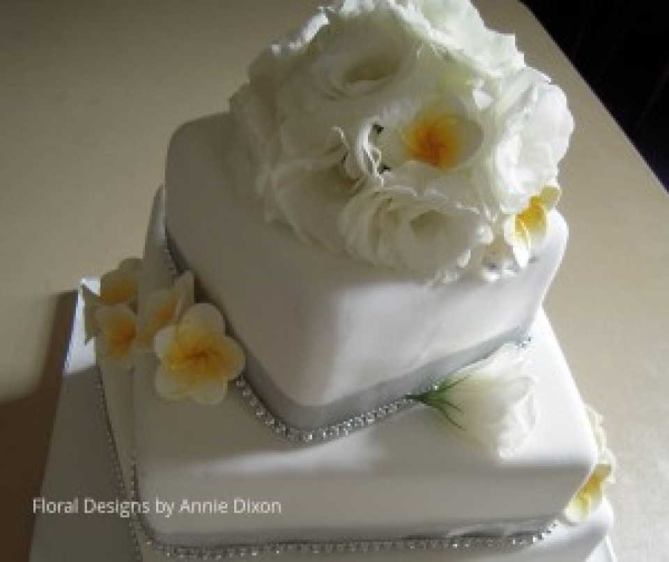 3 tier square wedding cake decorated with Lisianthus and Frangapanni decorations