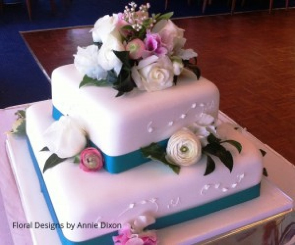 2 tier square wedding cake decorated with pink and white Spring flowers