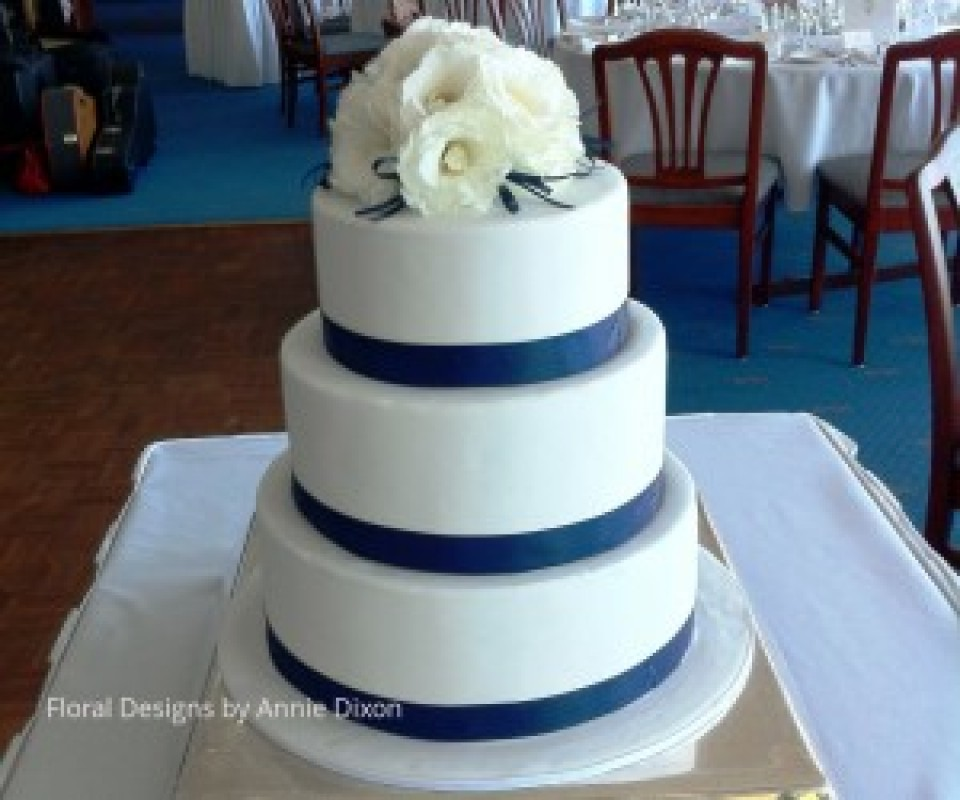 3 tier round wedding cake decorated with white Lisianthus and navy ribbon