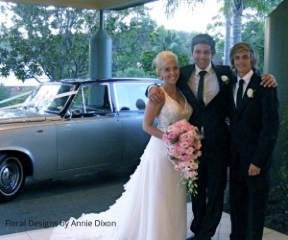 Bride holding a pastal pink teardrop bouquet, with the groom and his best man