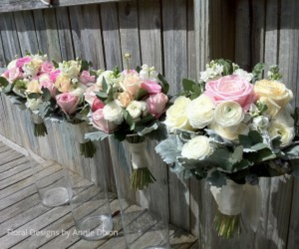 Bride and bridesmaids' posies of mixed pastal spring flowers including ranunculus and roses