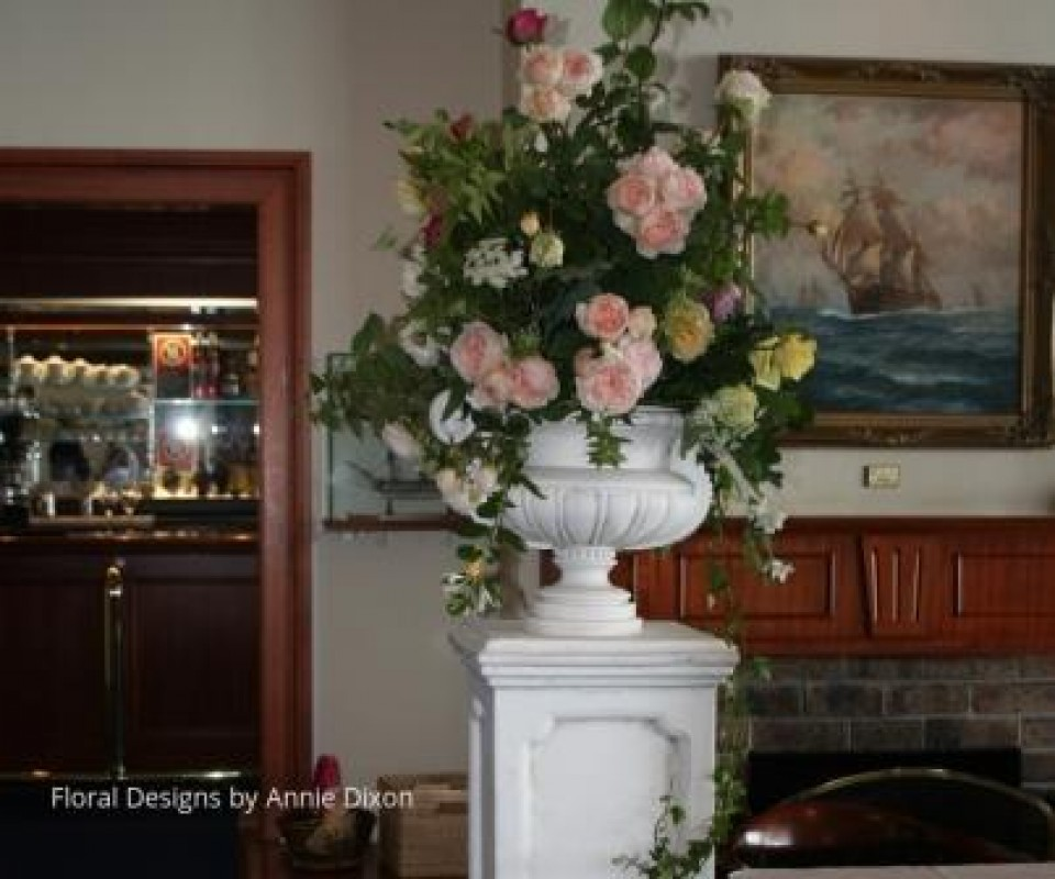 Classic urn arrangement of rambling roses on stone pedestal