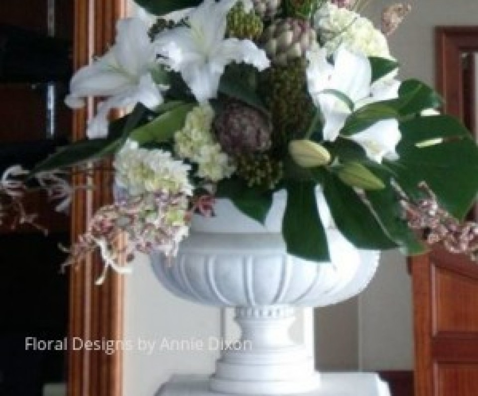 An arrangement of artichokes, Casablanca Lilies, Spider Orchids and Hydrangea in a classic urn