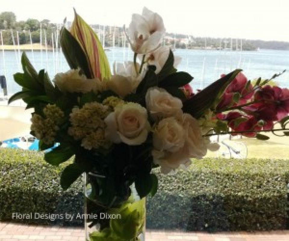 A glass cylinder arrangement of Cymbidiums, Roses and Hydrangea in bay window