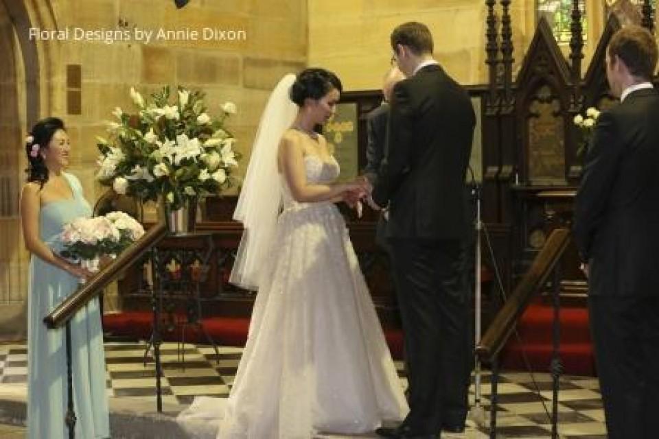 Church pedestal arrangement beside couple taking their vows
