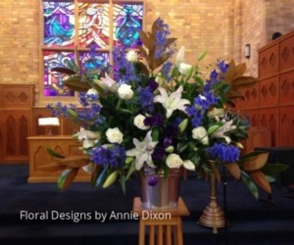 Large blue and white pedestal pedestal arrangement of Oriental lilies, Delphiniums and Roses in PLC chapel