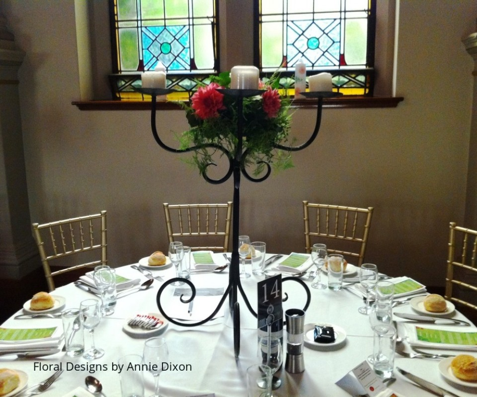 Wrought iron candelabra arrangement of dahlias with trailing aspagarus fern