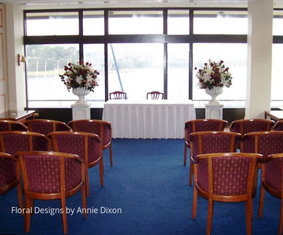 Indoor wedding ceremony set up including two classic urn pedestal arrangements