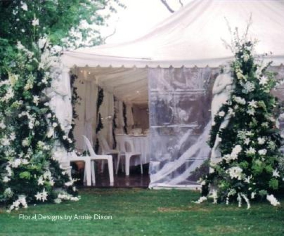 Garden statues decorated with flowers at entrance to wedding marquee