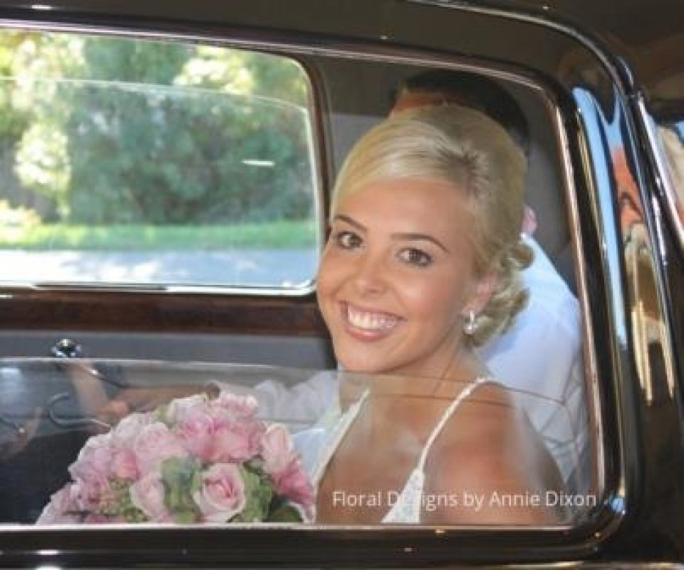 Bride and her pink bouquet inside the wedding car