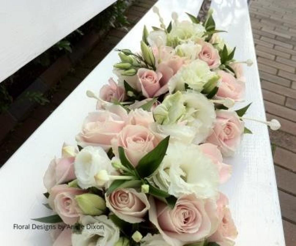 Flowergirls' posies of Sweet Avalanche roses, lisianthus and bouvardia